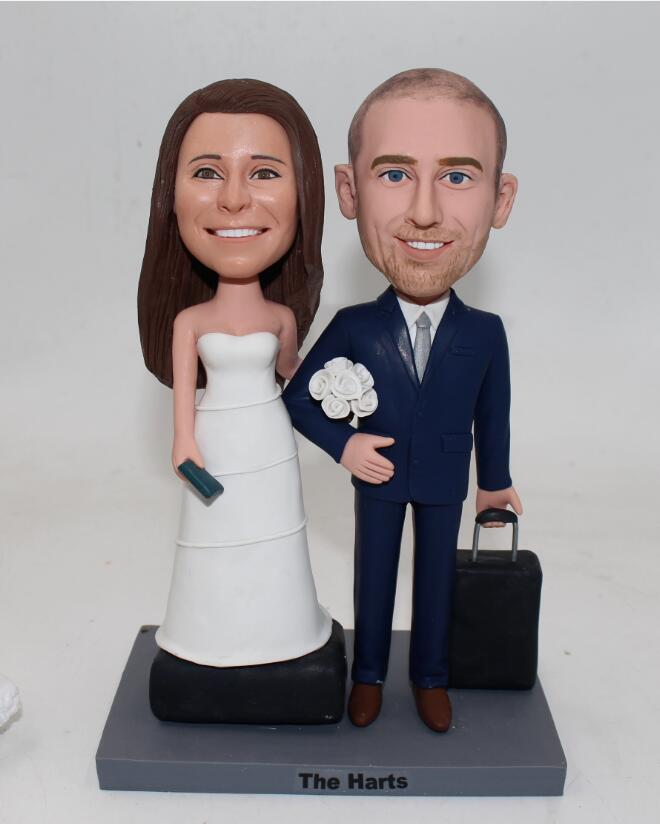 Travel themed wedding bobblehead cake toppers